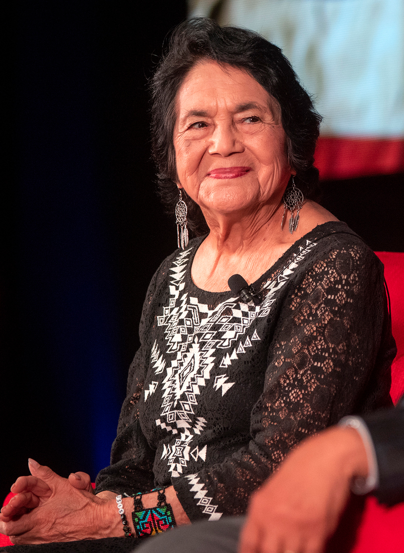 Picture Description: A Hispanic woman with black hair, smiling at the camera 90 years young. Dolores is wearing a black and white patterned blouse and long silver earrings.