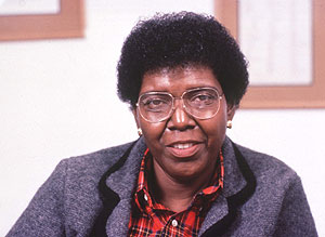 Picture Description: Congresswoman Barbara Jordan is a proud black woman with short black hair wearing glasses. She has a wonderful smile and is wearing a red plaid button-up shirt with a grey jacket.